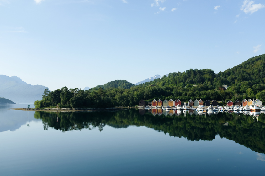A fjord landscape with colorful boathouses and their mirror reflection