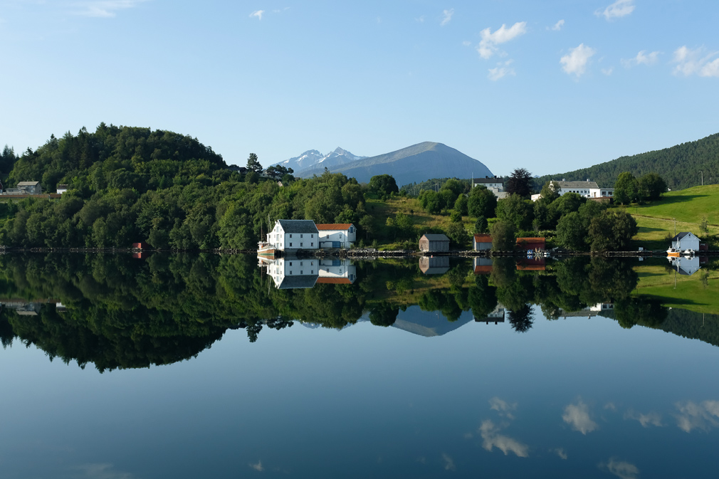 A fjord landscape with farmhouses and their reflections mirrored by the water