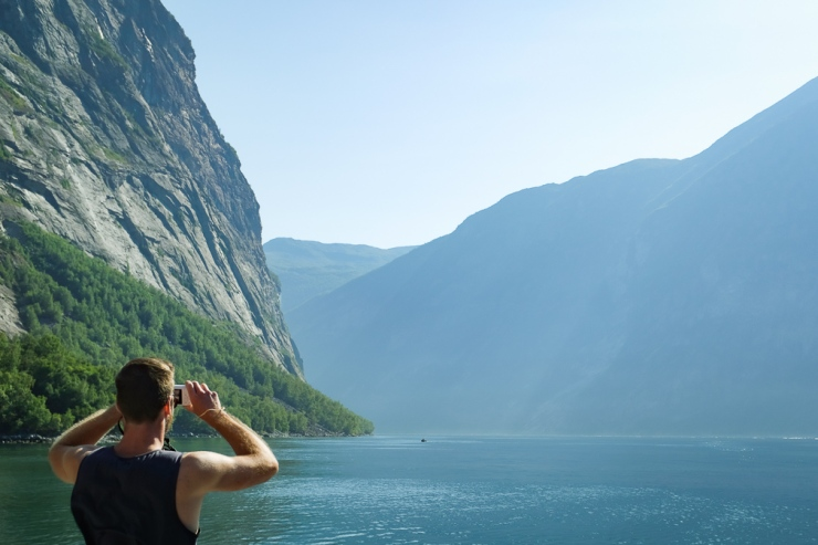 Man taking a panoramic photo of a fjord landscape