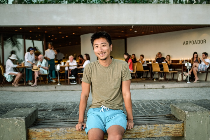 Smiling man sitting in front of outdoor hotel restaurant
