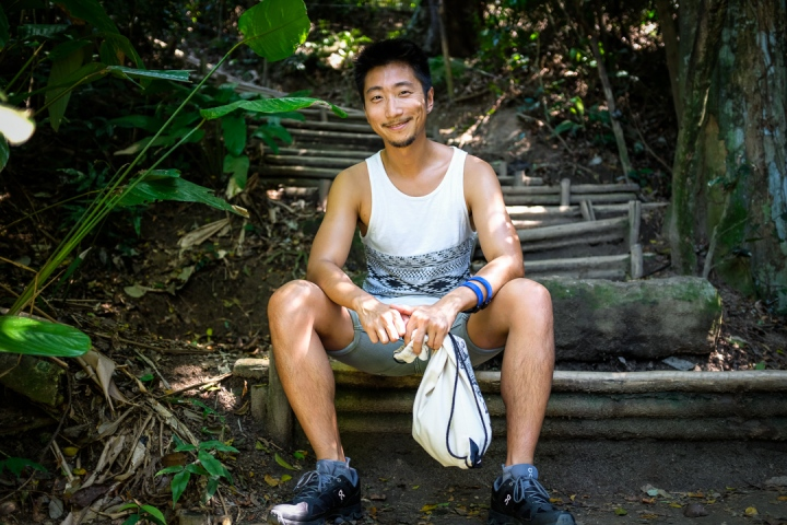 Smiling man sitting in front of jungle pathway