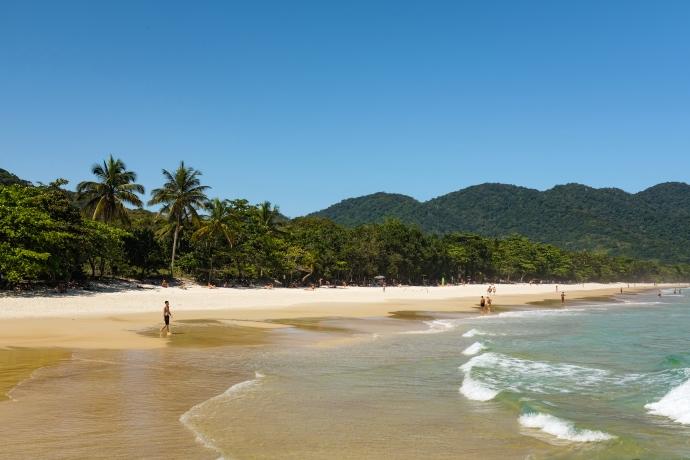 People enjoying a pristine, sandy beach by tropical hills