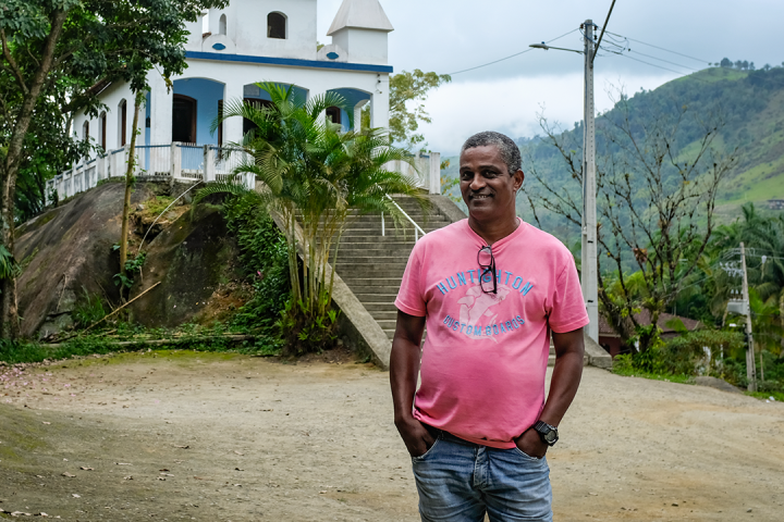 Man in pink shirt posing in front of a church