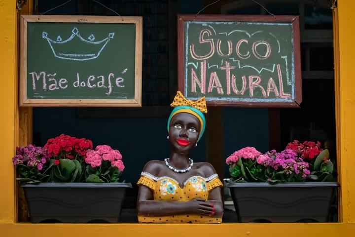 "A Brazilian sculpture called ""Namoradeira"" perched on a windowsill"