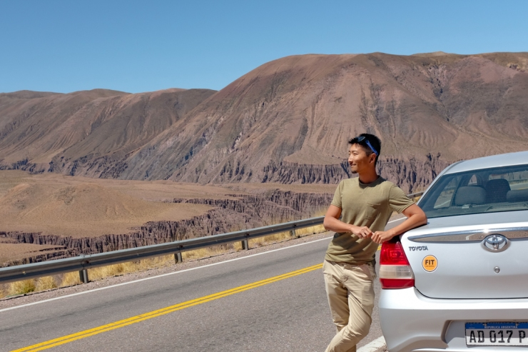 Man posing by car in front of canyon landscape