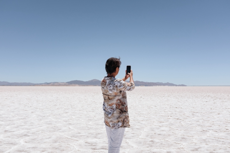 A woman taking a photo of salt flats