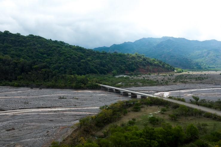 A bridge crossing a dried out river in a jungle-clad valley landscape