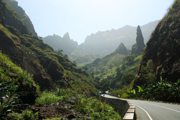 A paved road leading into a green, mountainous valley