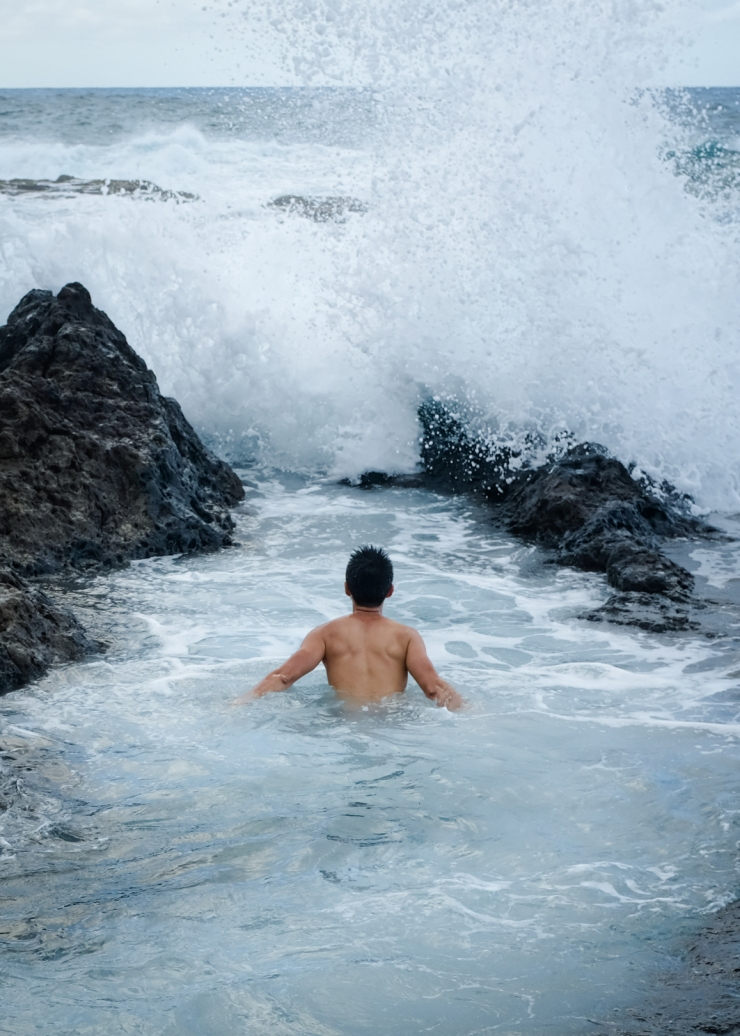 A man swimming in a natural rock pool