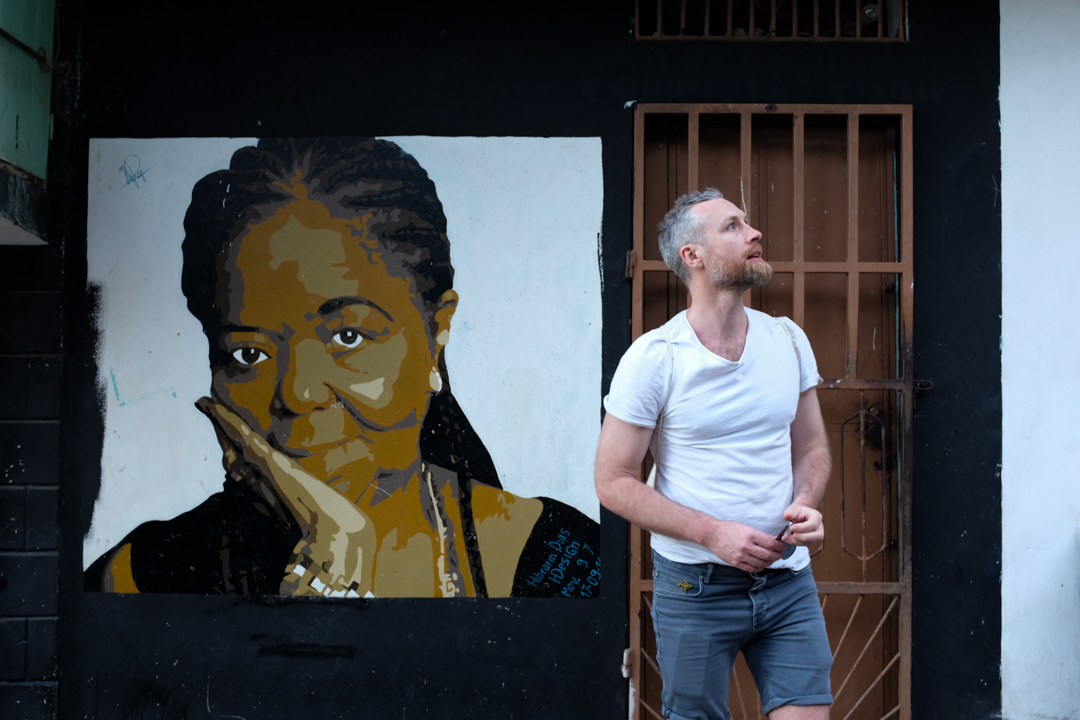 Man in white shirt in front of a painting of Cesária Evora
