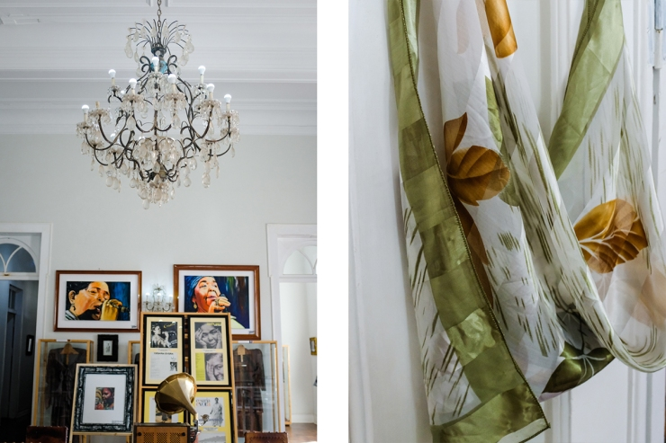 A chandelier and pictures of a woman singing hang in a room and a close-up of a green and gold shawl