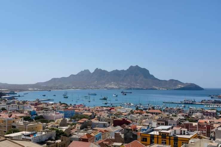 A colonial-style town and harbor set to the backdrop of jagged mountain peaks