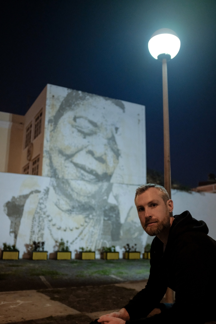 A man sitting in front of a mural