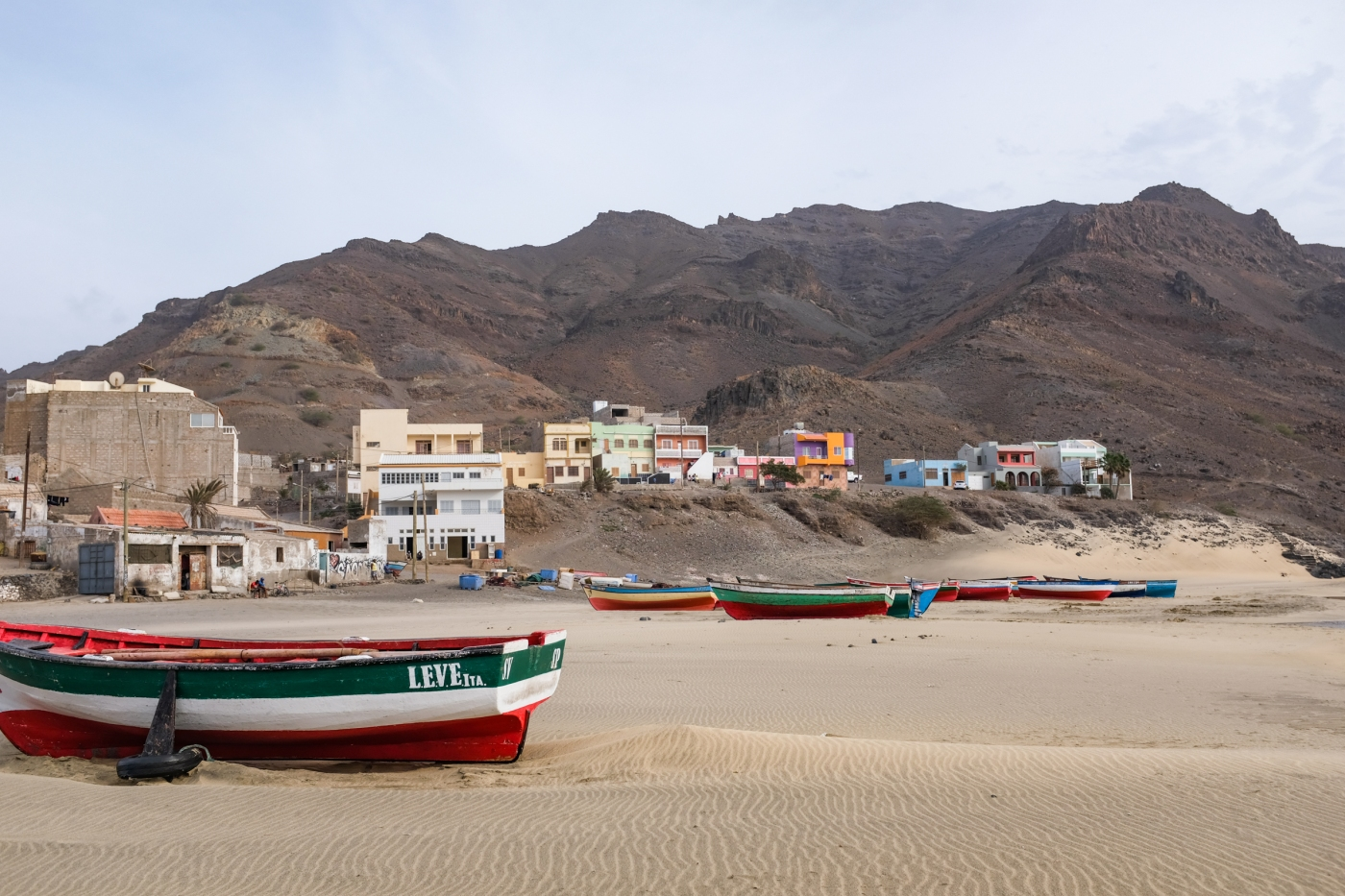 Painted boats on a sandy beach in front of a small fishing village