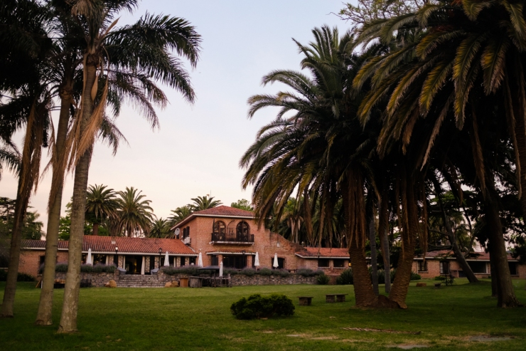 A hacienda with palm trees at sunset