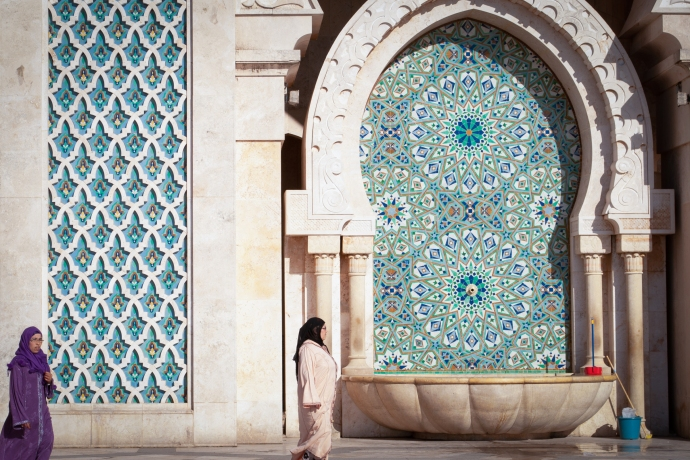 Women in hijab walk in front of zellige tilework
