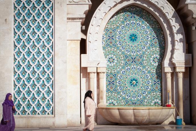 Women in hijab walk in front of zellige tilework