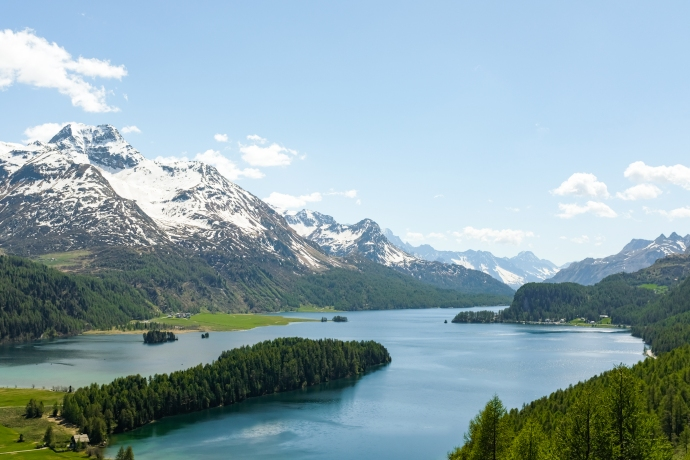 A forested peninsula juts into an alpine lake