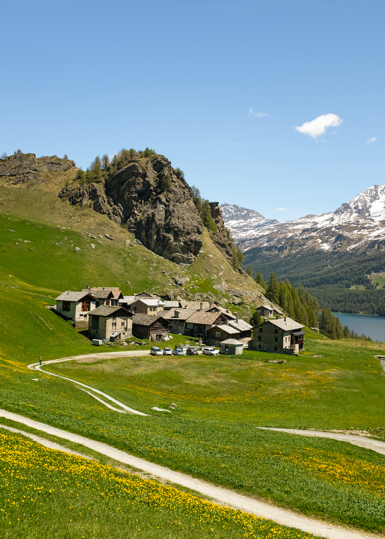 A hiking path leading to a small mountain village in an alpine pasture