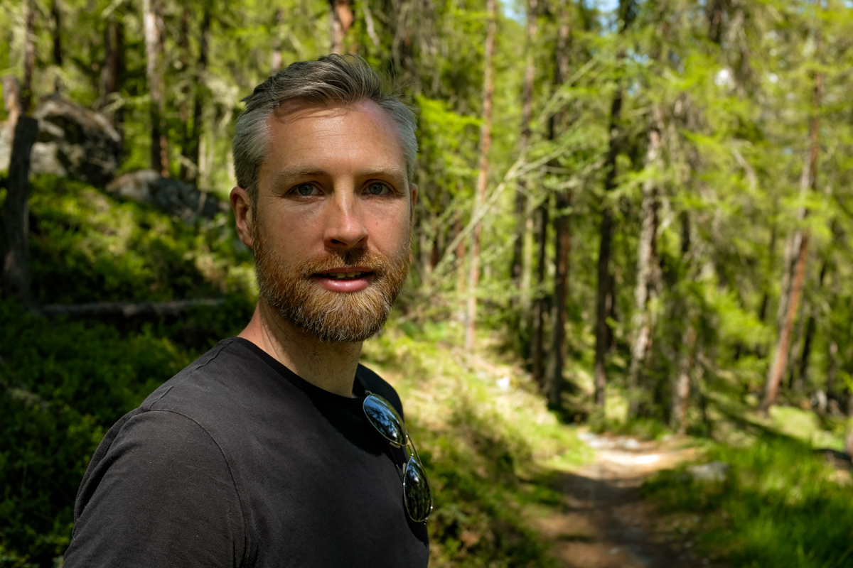 A man looking into the camera on a forested path