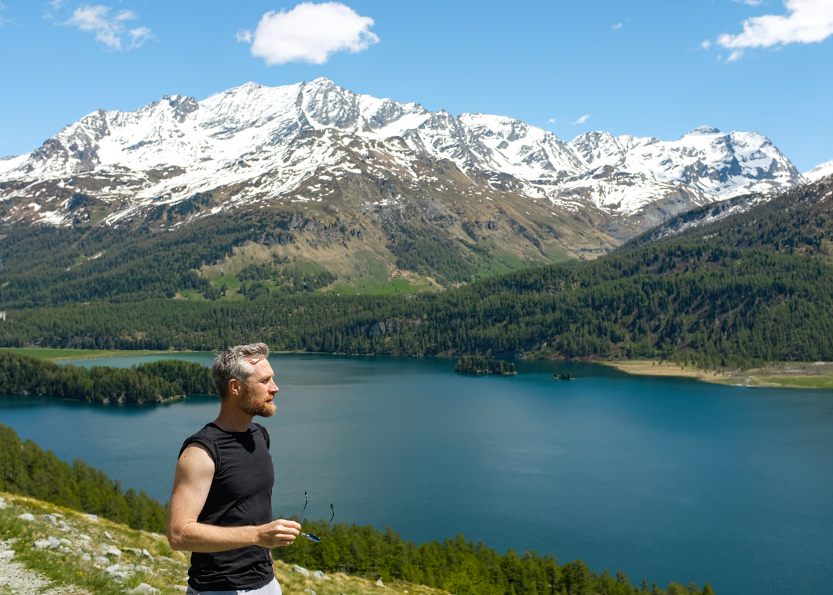 A man looking at the scenery of a mountain lake