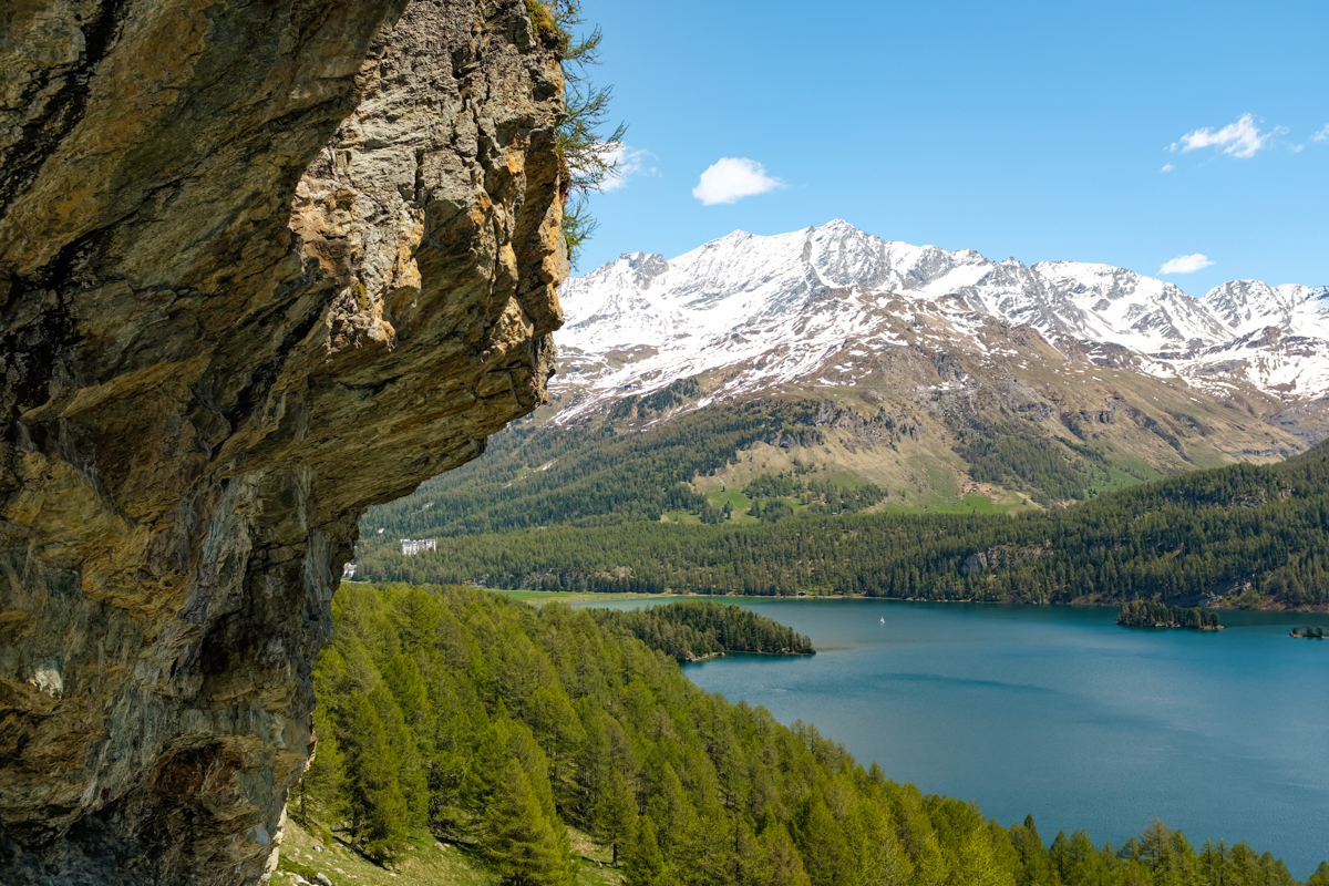 A rock overhang in front of a view of forests, mountains, and a lake