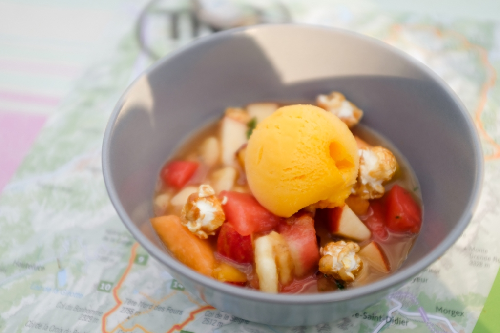 A dessert of watermelon, melon, apples, caramelized popcorn, and ice cream