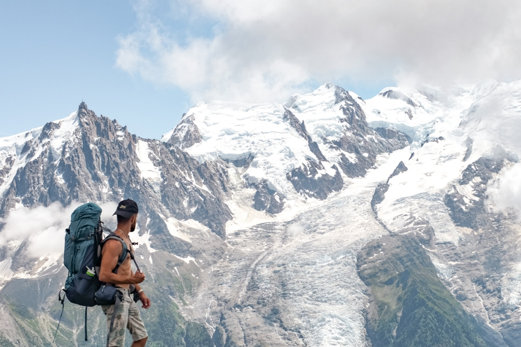 Man in backpack looks at a glacier