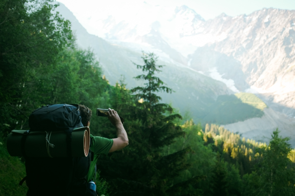 Man with camping backpack takes a photo of the mountains