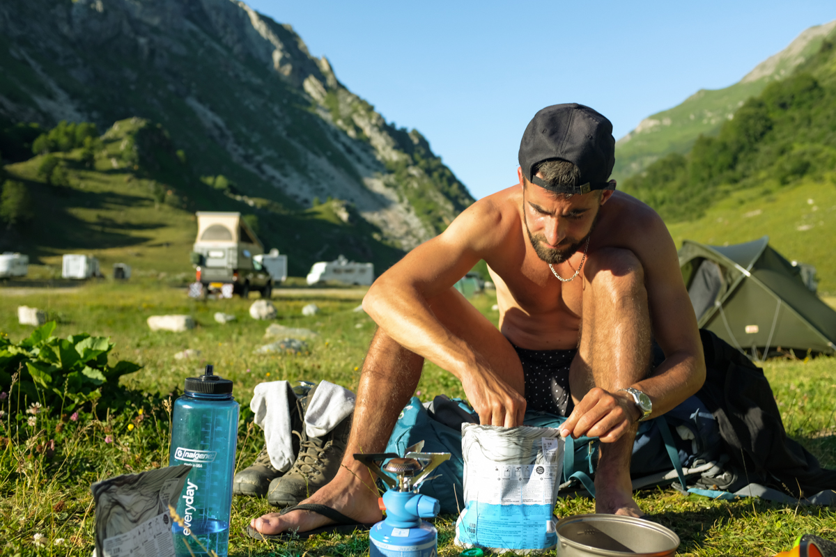 Man in cap prepares portable camping stove in a mountain valley