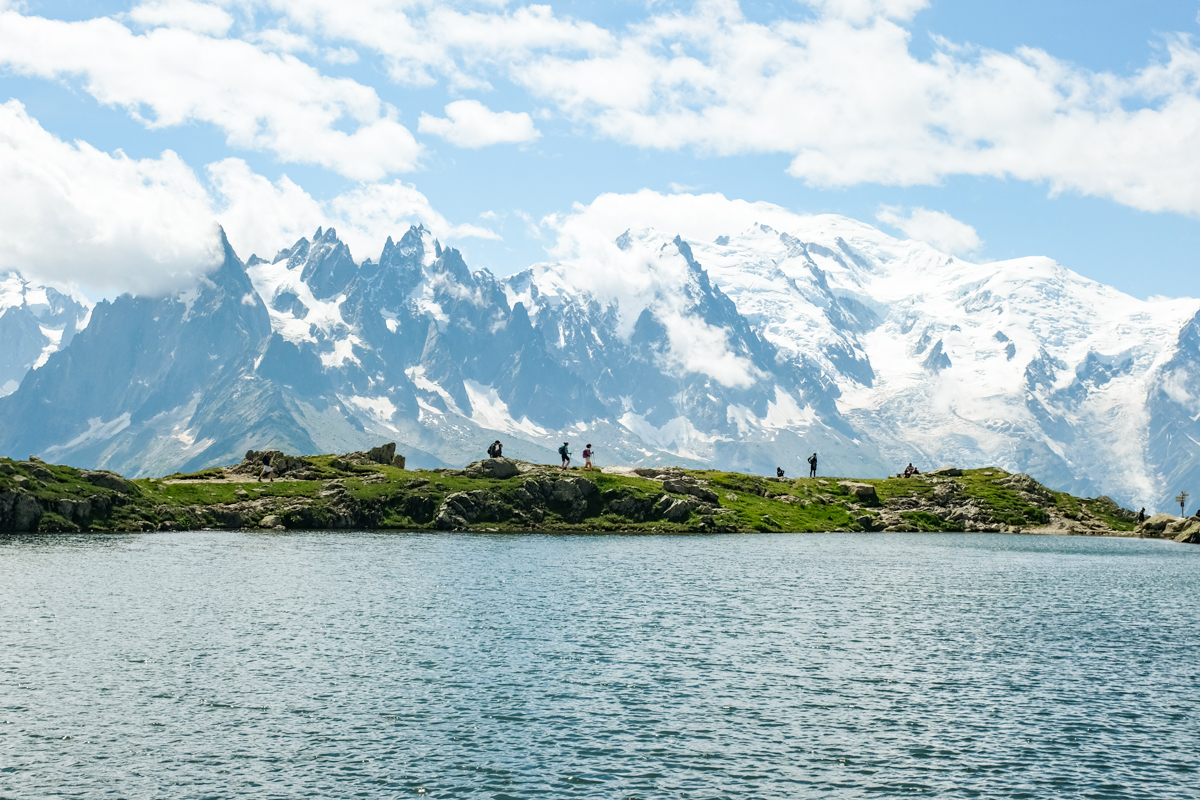 Hikers walking along an alpine lake in front of glaciers and mountain peaks