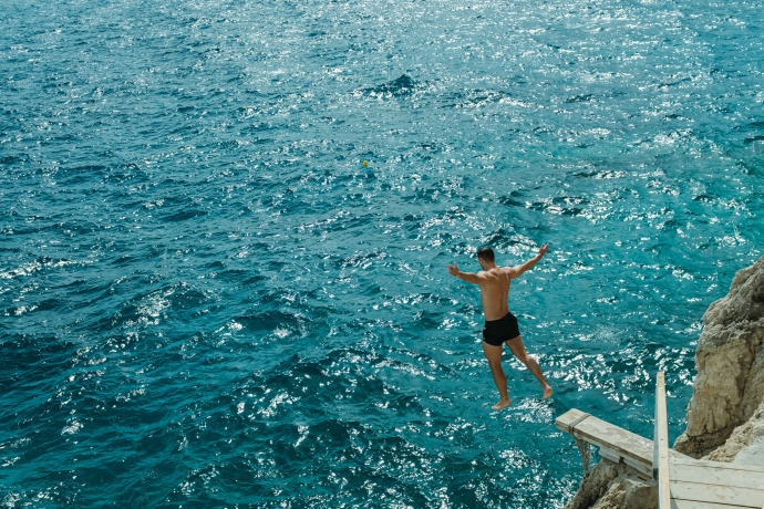 A man diving from a wooden plank into the ocean