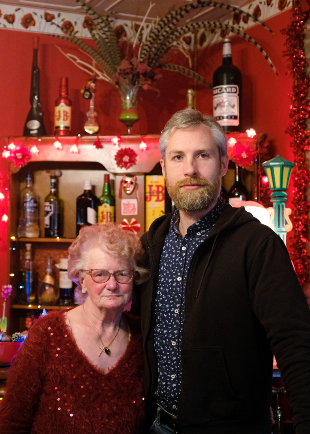 A man and elderly woman post in front of a red living room