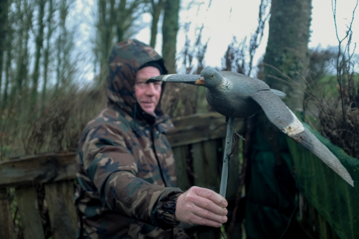 A man in camo holds up a decoy pigeon