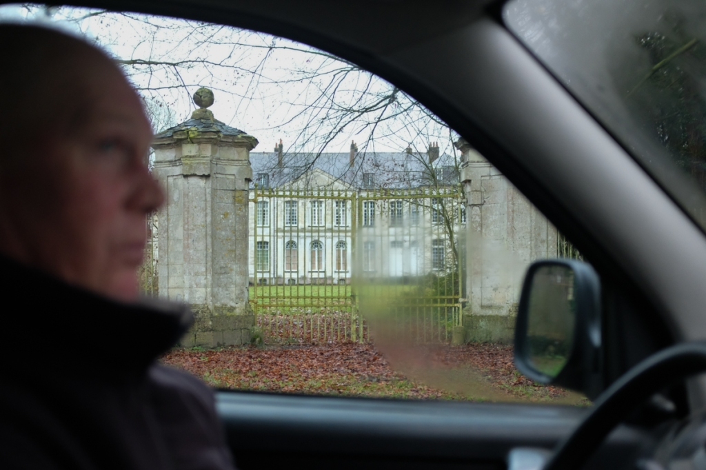 Man sitting in car in front of gated chateau