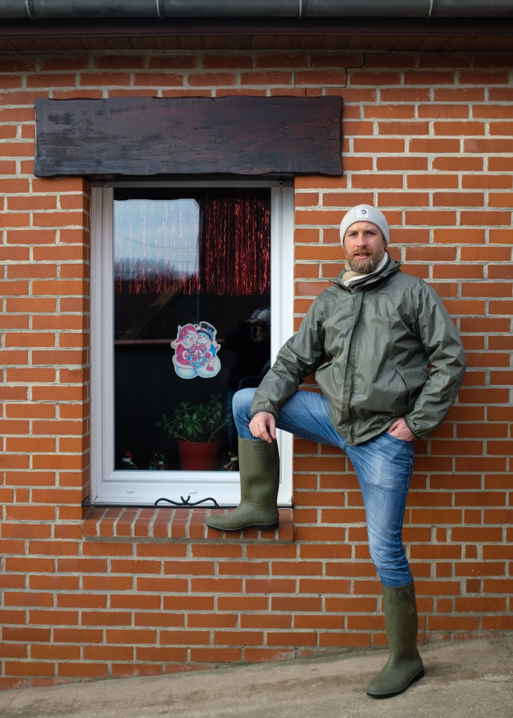 Man in rain jacket and boots posing in front of a brick house
