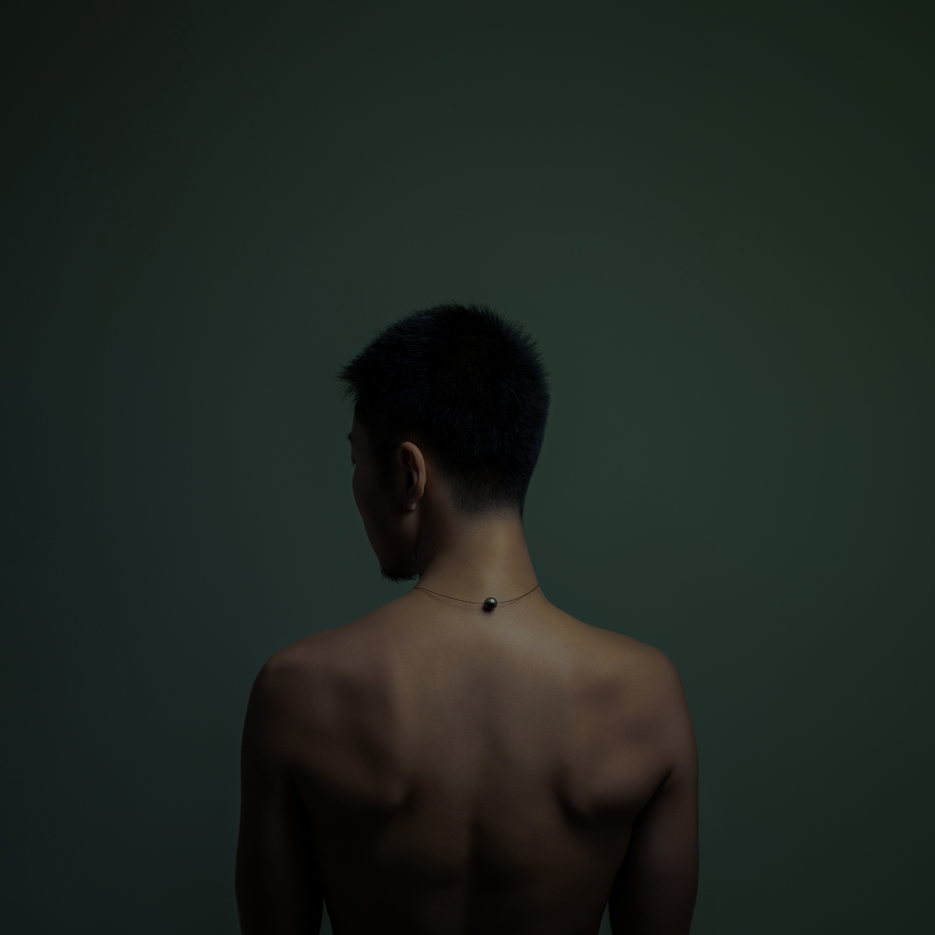 The back of a man with a pearl necklace