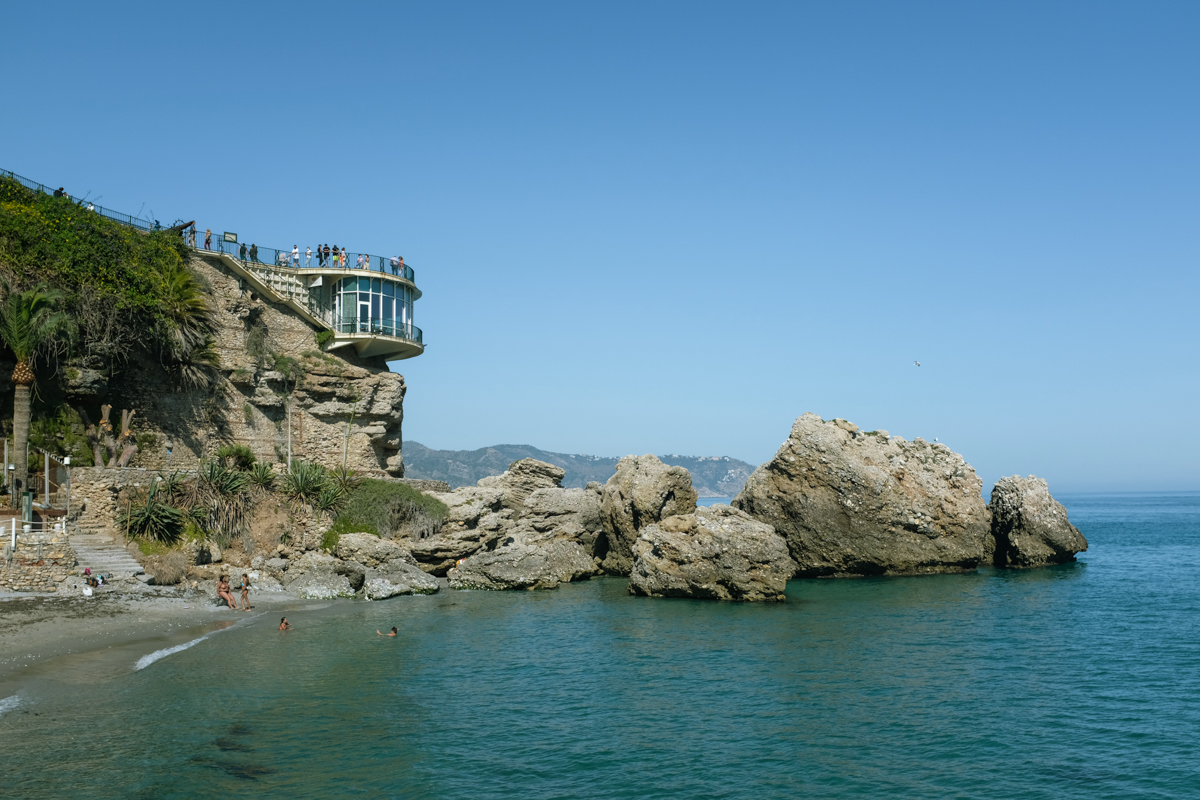 A glass building atop a rocky promontory by the beach