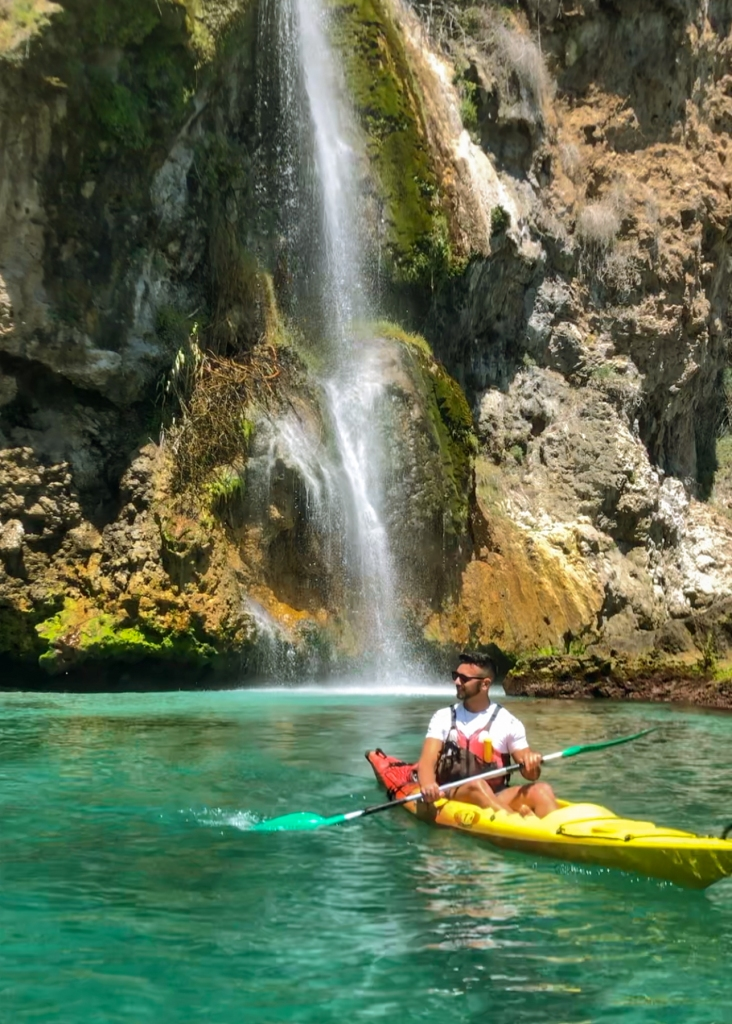 A man in a kayak resting by a waterfall