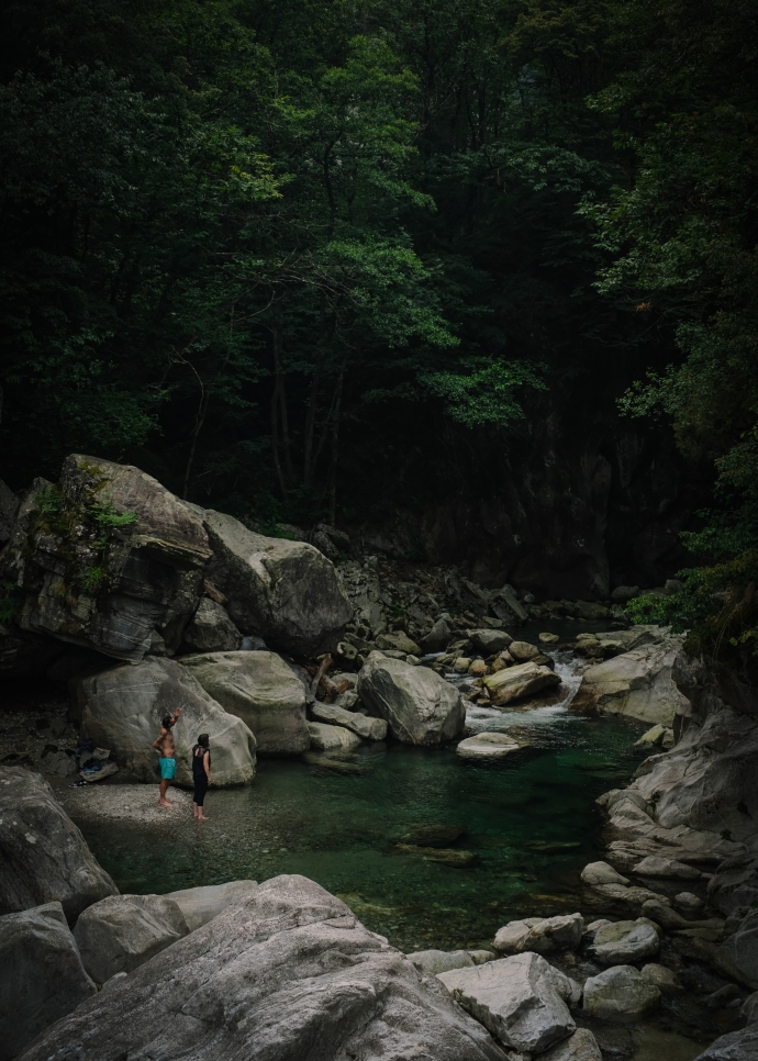 Two people by a swimming hole looking towards a dark forest