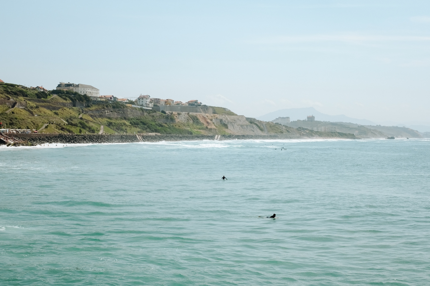 Surfers paddling near the coast on a sunny day