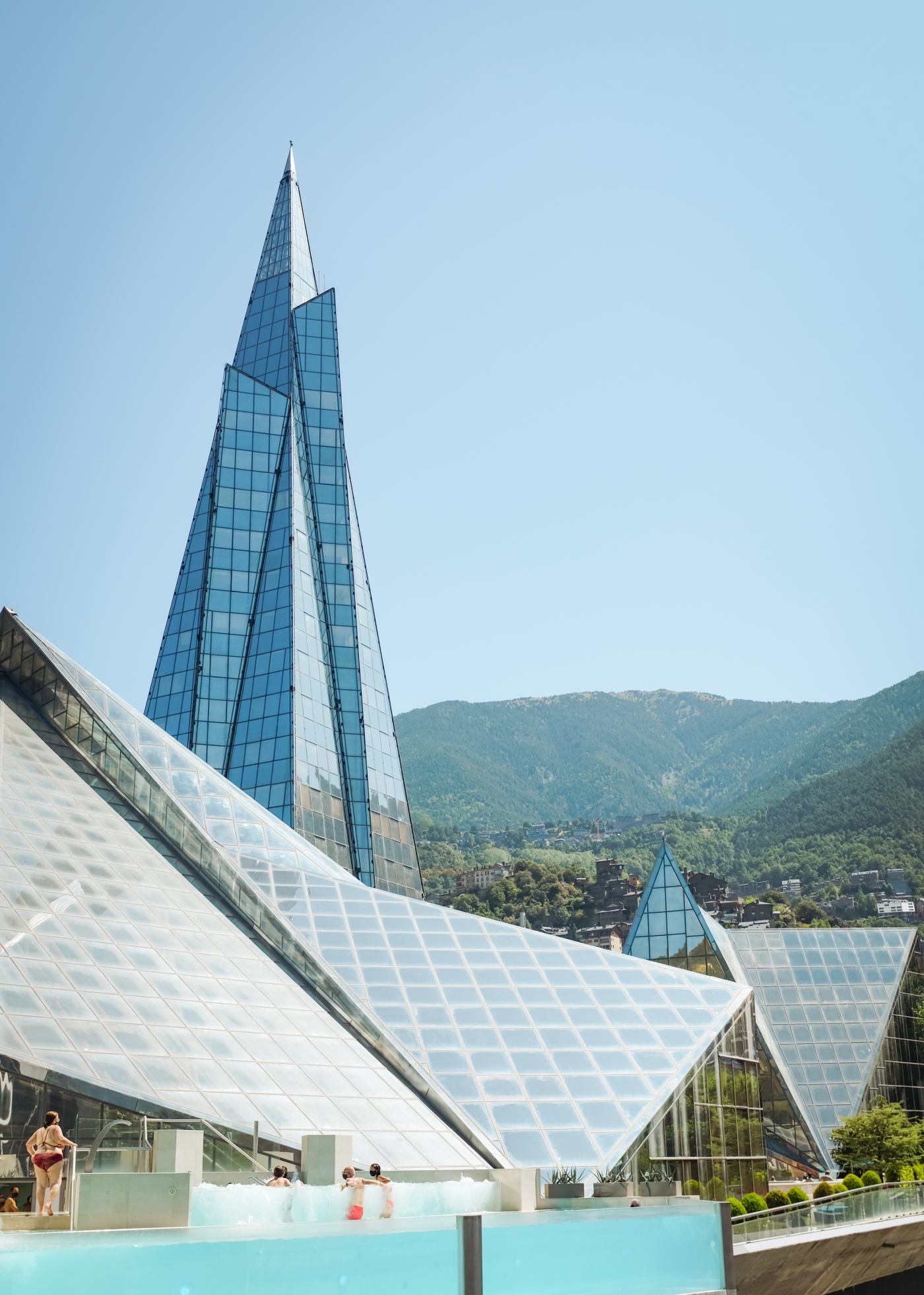 A tall, glassy spire behind a thermal spa complex