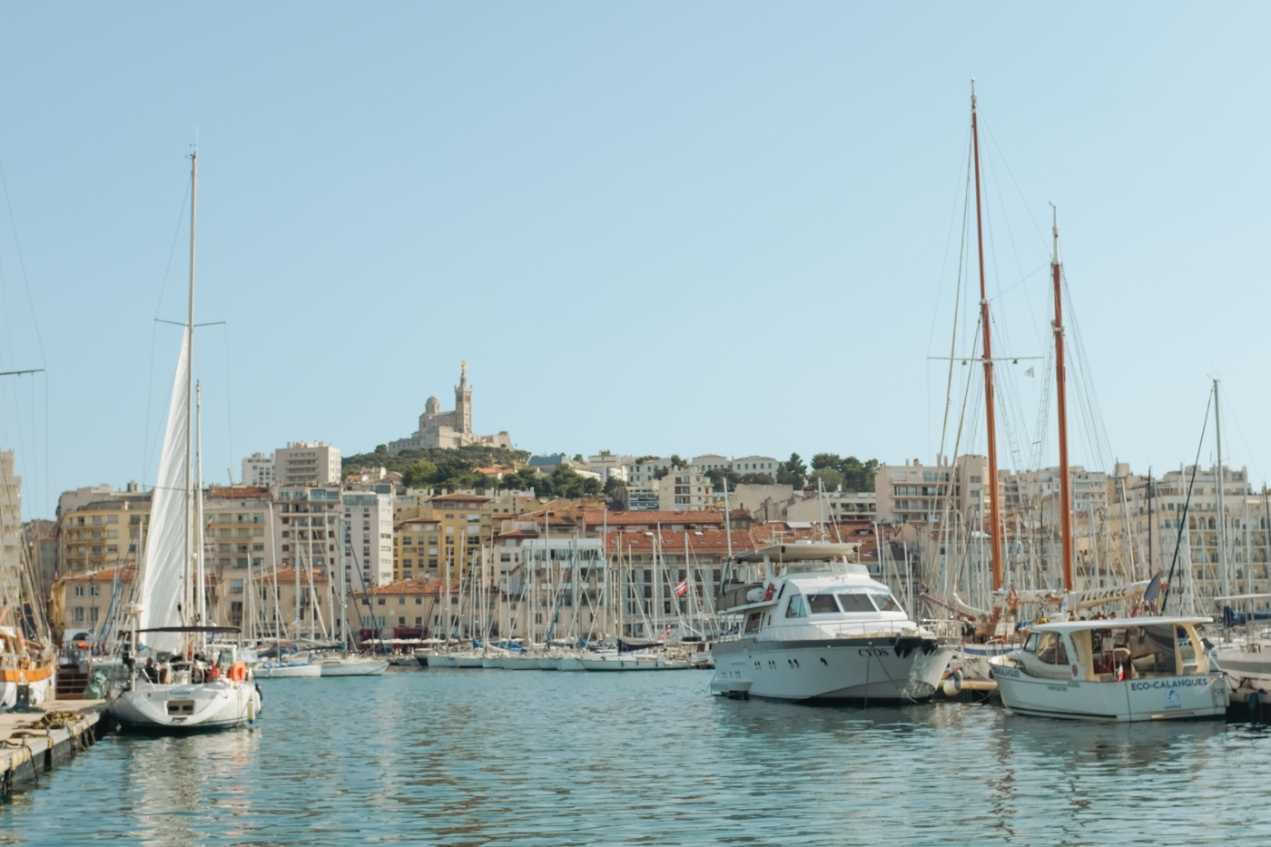 European harbor with a basilica atop a green hill in the distance